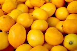 Pile of ripened Meyer Lemons that are bright yellow.